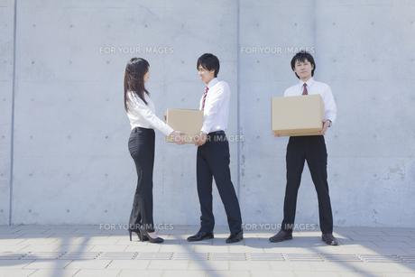 段ボールを運ぶビジネスマンとビジネスウーマンの写真素材 [FYI00468838]