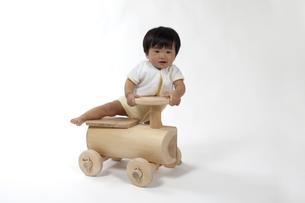 木の車のおもちゃに乗る赤ちゃんの写真素材 [FYI00469136]