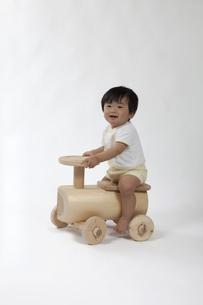 木の車のおもちゃに乗った赤ちゃんの写真素材 [FYI00469149]