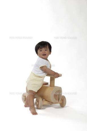 木の車のおもちゃを持って笑う赤ちゃんの写真素材 [FYI00469150]