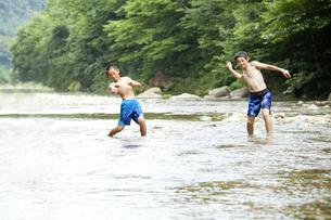 川の小石で水切り遊びをする子供たちの写真素材 [FYI00469523]
