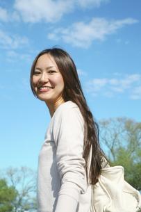 青空のもと微笑む女性の写真素材 [FYI00470193]