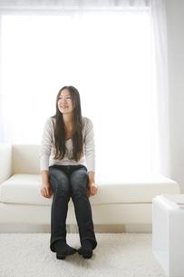 ソファーに座ってくつろぐ女性の写真素材 [FYI00470208]