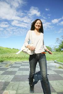 歩く女性と青空の写真素材 [FYI00470213]