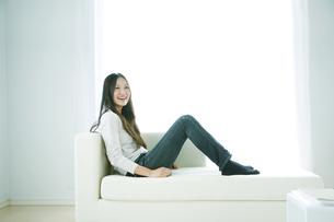 ソファーに座ってくつろぐ女性の写真素材 [FYI00470215]