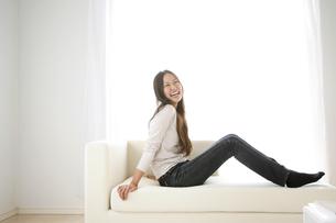 ソファーに座ってくつろぐ女性の写真素材 [FYI00470222]