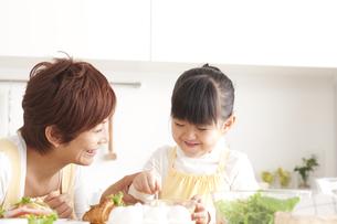 キッチンでサンドウィッチを作る母娘の写真素材 [FYI00470259]