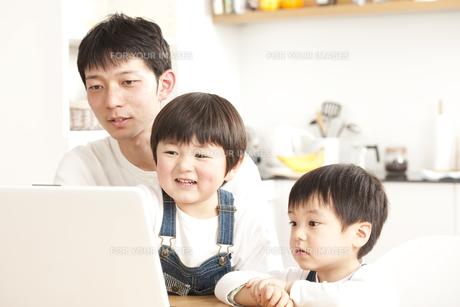 ダイニングキッチンでパソコンを見る親子の写真素材 [FYI00470268]
