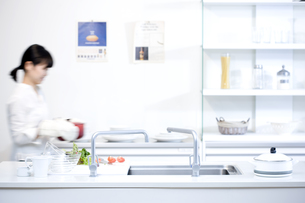キッチンで鍋を運んでいる女性の写真素材 [FYI00470335]