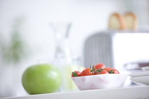 テーブルに置かれたトースターとミニトマトと青りんごの写真素材 [FYI00470347]