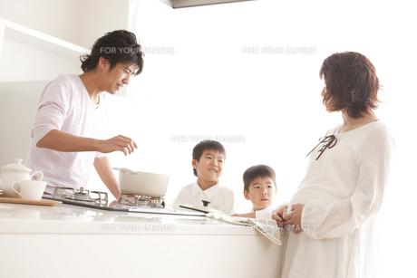 ガスキッチンを囲む親子の写真素材 [FYI00470378]