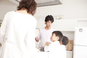 ガスキッチンを囲む親子の写真素材 [FYI00470385]