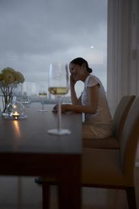 ワイングラスと窓辺に座る女性の横顔の写真素材 [FYI00470726]