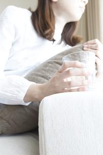 窓際のソファーでグラスを持つ女性の写真素材 [FYI00471181]