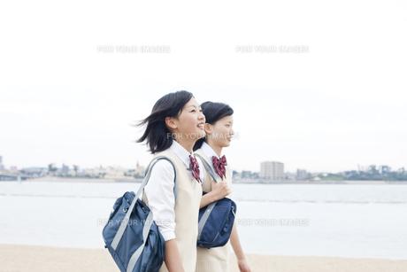 海沿いを歩く女子高校生二人の写真素材 [FYI00471192]