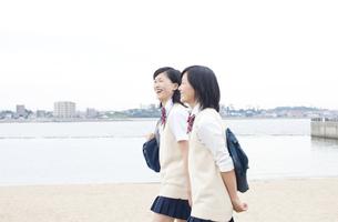 海沿いを歩く女子高校生二人の写真素材 [FYI00471225]