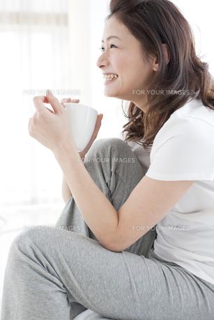 マグカップを持った笑顔の女性の写真素材 [FYI00471263]