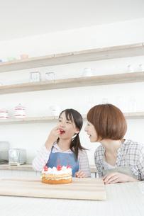スポンジケーキを前にチェリーをほおばる女の子と笑顔の母親の写真素材 [FYI00471267]