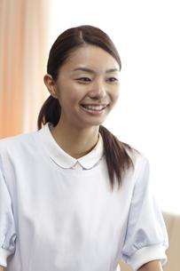 窓辺に立つ笑顔の女性介護士の素材 [FYI00471269]