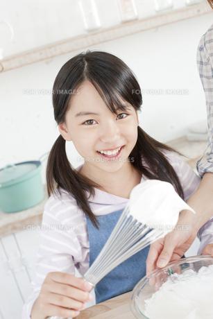 泡立て器についたクリームを見せる女の子の写真素材 [FYI00471271]