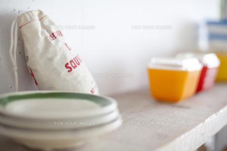 木の棚の陶器の皿と布袋とオレンジと赤の容器の素材 [FYI00471272]