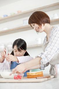 キッチンで泡立て器でホイップクリームを作っている女の子と母親の写真素材 [FYI00471274]