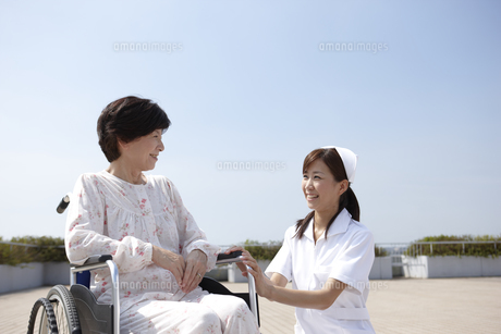青空と車椅子のシニア女性と笑顔で会話する看護師の写真素材 [FYI00471277]