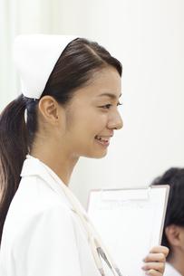 クリップボードを持った笑顔の女性看護師の横顔の写真素材 [FYI00471281]