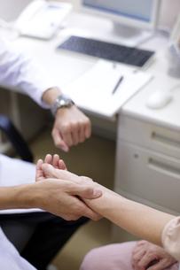 女性患者の脈をとる医師の写真素材 [FYI00471285]