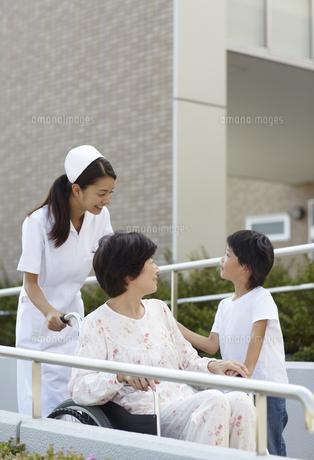 車椅子に乗ったシニア女性と話をする男の子の写真素材 [FYI00471296]