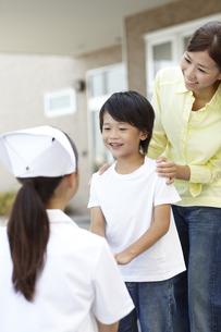 病院の玄関で女性看護師に見送られる男の子と母親の写真素材 [FYI00471297]