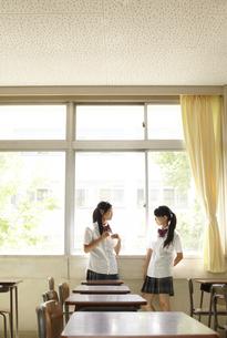 教室の窓際に立って話をしている女子高生二人の素材 [FYI00471311]