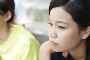 Tシャツを着た女子高生の遠くを見つめる眼差しの写真素材 [FYI00471312]