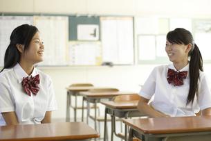 教室の机に座り話をしている笑顔の女子高生二人の写真素材 [FYI00471313]