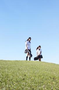 青空の下の芝の高台に立つ女子高生の写真素材 [FYI00471317]