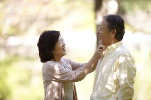 緑の中で夫の襟を直す妻の写真素材 [FYI00471321]