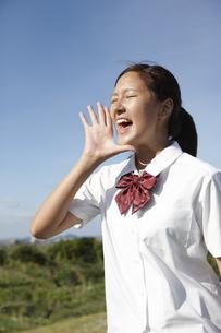 青空の下の芝の高台でおもいっきり叫ぶ女子高生の写真素材 [FYI00471323]