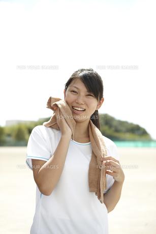 学校のグラウンドでタオルで汗を拭くTシャツの女子高生の写真素材 [FYI00471327]