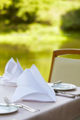 テーブルに置かれた食器類と三角に折られたナプキンの写真素材 [FYI00471330]