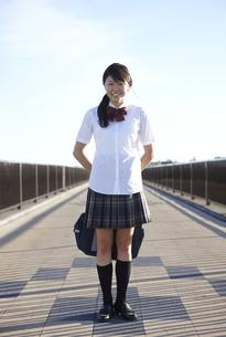 歩道の中央に立つ女子高生のポートレートの写真素材 [FYI00471331]