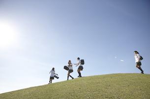 青空の下の芝の高台でふざけ合う女子高生四人の写真素材 [FYI00471332]