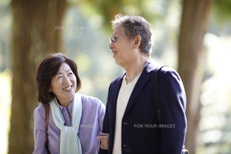 腕を組み笑顔で歩くシニア夫婦の写真素材 [FYI00471338]