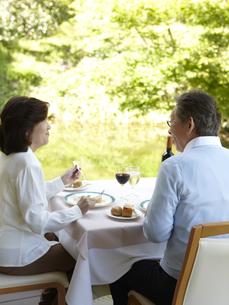 池を望むテラスで食事をしているシニア夫婦の写真素材 [FYI00471341]