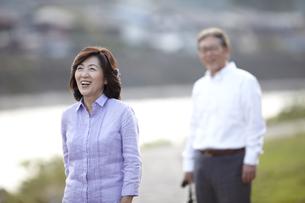 川岸の歩道で笑顔の妻の後姿を見ているシニア男性の写真素材 [FYI00471345]