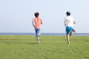 海辺の芝生の上を海へ向かって走る若者二人の写真素材 [FYI00471362]