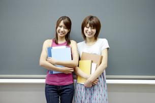 黒板の前に立つノートを抱えた女子大生二人のポートレートの写真素材 [FYI00471367]