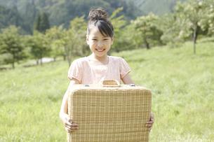 草原でバスケットを持つ女の子の写真素材 [FYI00471388]