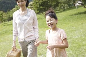 バスケットを持って草原を歩く母と子の写真素材 [FYI00471414]