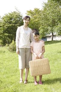 バスケットを持って草原に立つ母と子の写真素材 [FYI00471421]