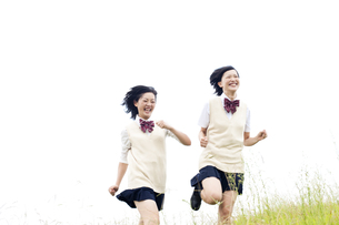 草原を走る女子高校生二人の写真素材 [FYI00471425]